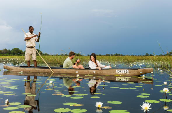 Discovering the Okavango Delta waterways by mokoro canoe.