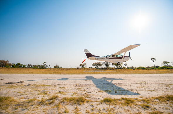 Light aircraft taking flight from bush airstrip.