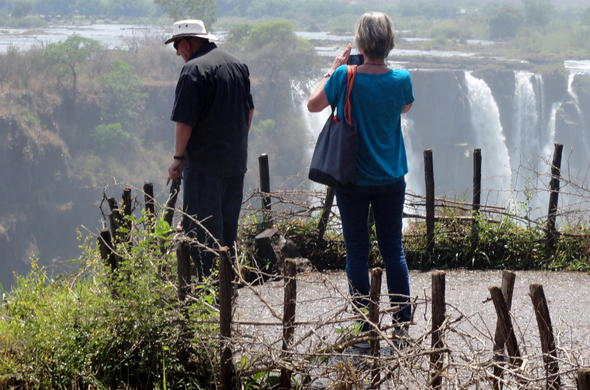Travellers admiring the Victoria Falls in Zimbabwe.